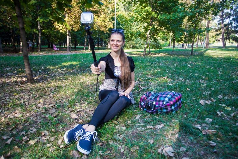 Jeune jolie fille s'asseyant sur l'herbe et prenant le selfie sur un appareil-photo d'action photographie stock libre de droits