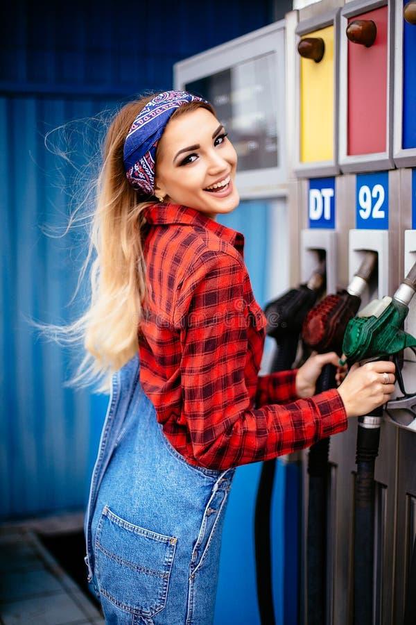 Jeune jolie fille travaillant à une station service photo stock