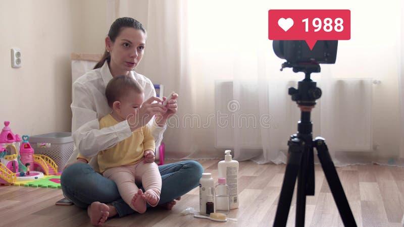 Jeune jolie mère avec le vlog de enregistrement ou faire de bébé le virel vivant de courant et de aller avec le compteur aimé 4k photos stock