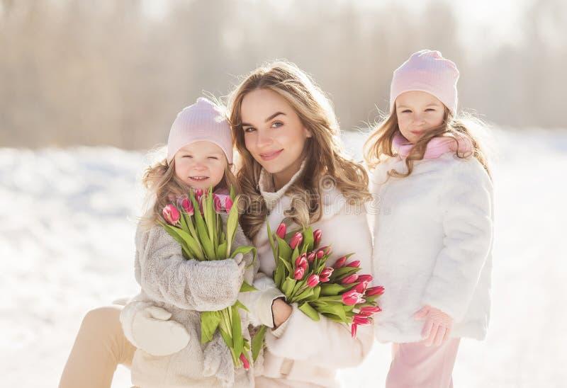 Jeune jolie mère avec petites filles et tulipes dans mains pendant l'hiver image stock