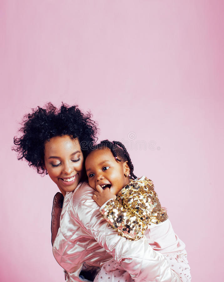Jeune jolie mère d'afro-américain avec la petite fille mignonne étreignant, sourire heureux sur le fond rose, mode de vie images stock