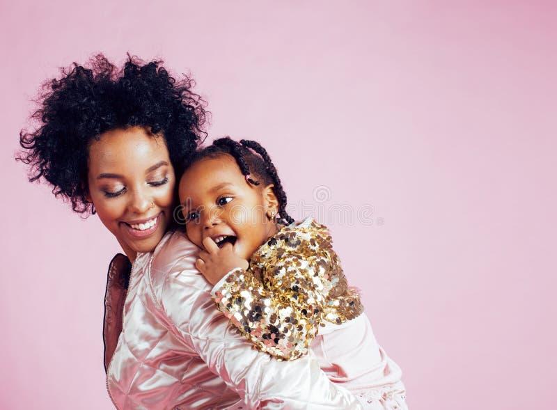 Jeune jolie mère d'afro-américain avec la petite fille mignonne étreignant, sourire heureux sur le fond rose, mode de vie photos stock
