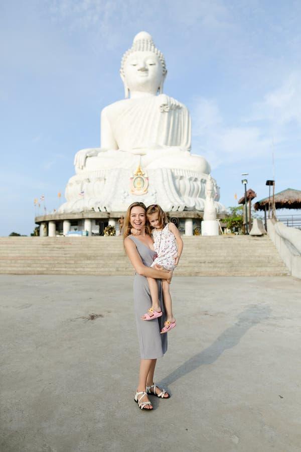 Jeune jolie mère se tenant avec la petite fille près de la statue concrète de Bouddha à Phuket photo libre de droits