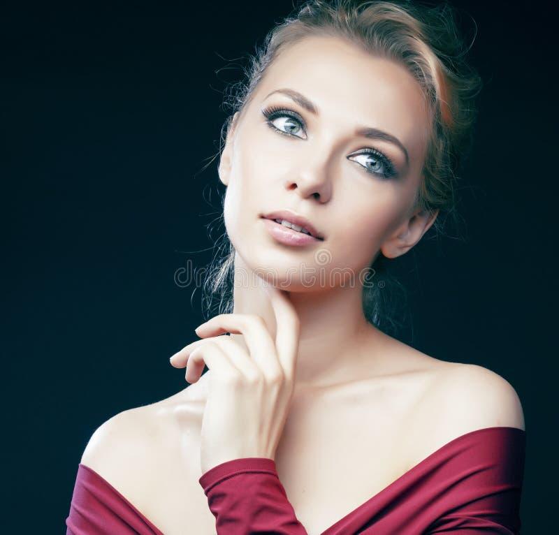 Jeune jolie pose blonde de fille sensuelle sur le fond noir dans la combinaison rouge, concept de personnes de mode de vie images stock