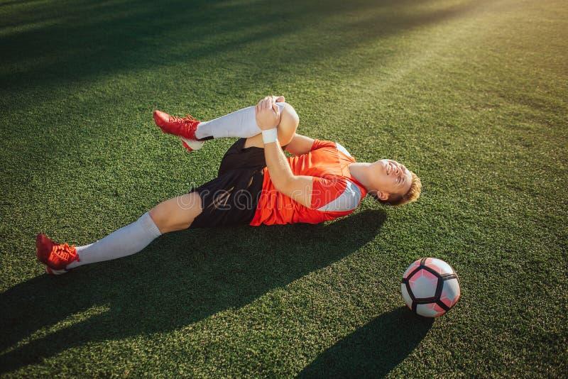 Jeune joueur de football se trouvant sur la jambe de pelouse et de prise Il le tire à se Le type sent la douleur dans le genou Bo photos libres de droits