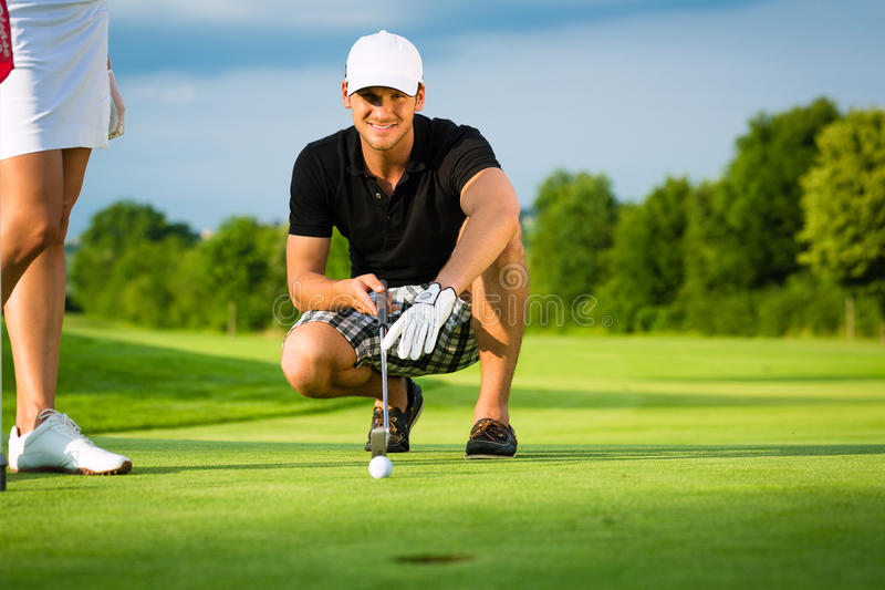 Jeune joueur de golf sur le cours mettant et orientant photos libres de droits