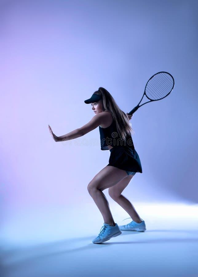 Jeune joueur de tennis disposant à faire le tir d'avant-main photographie stock libre de droits