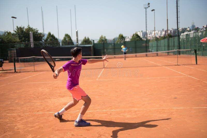 Jeune joueur de tennis jouant l'avant-main avec l'impact de hgh photos stock