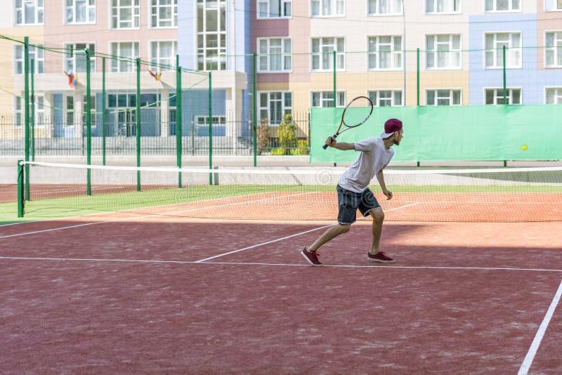Jeune joueur masculin de tannis courant sur la cour avec la raquette dans les mains image libre de droits