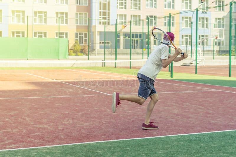 Jeune joueur masculin de tannis courant sur la cour avec la raquette dans les mains photo libre de droits