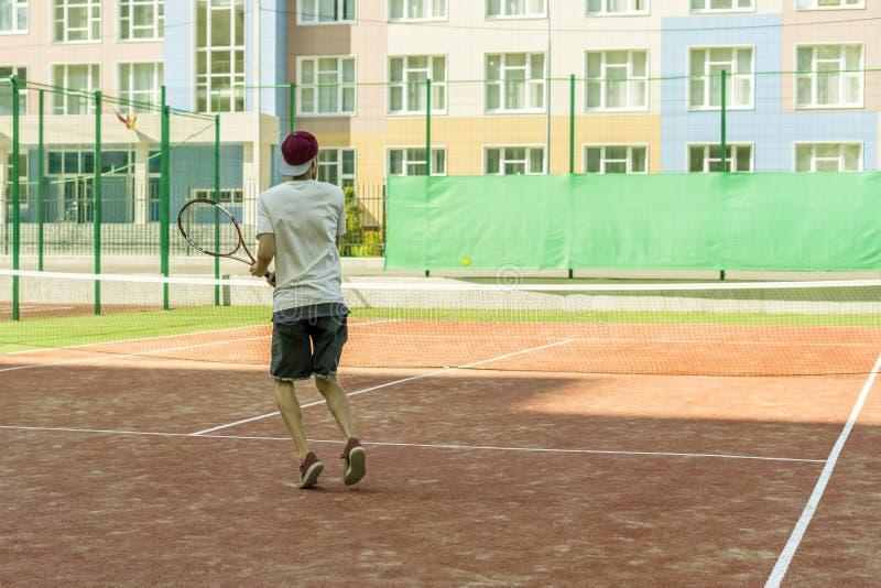 Jeune joueur masculin de tannis courant sur la cour avec la raquette dans les mains photo stock