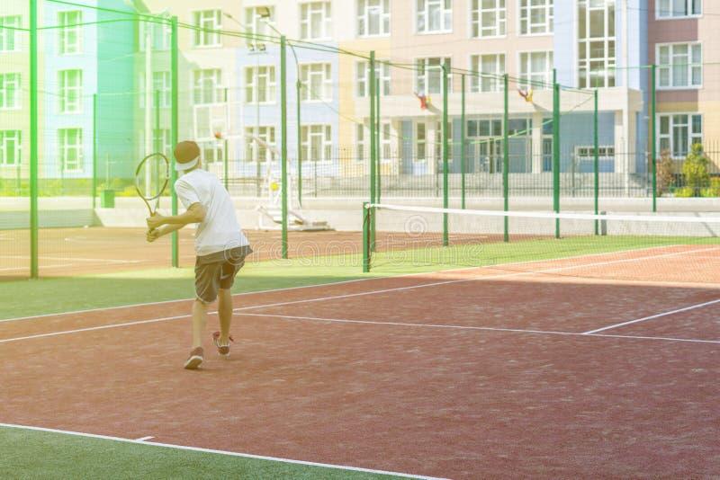 Jeune joueur masculin de tannis courant sur la cour avec la raquette dans les mains images stock
