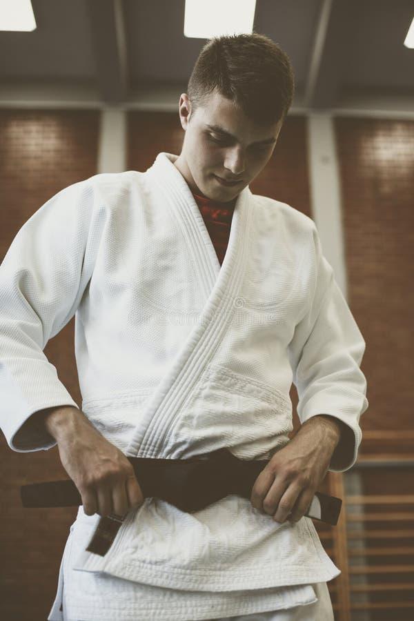 Jeune judo de pratique masculin dans le kimono image libre de droits