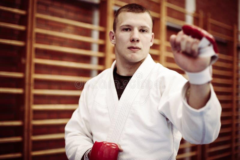 Jeune judo de pratique masculin dans le kimono avec le gant de combat image stock