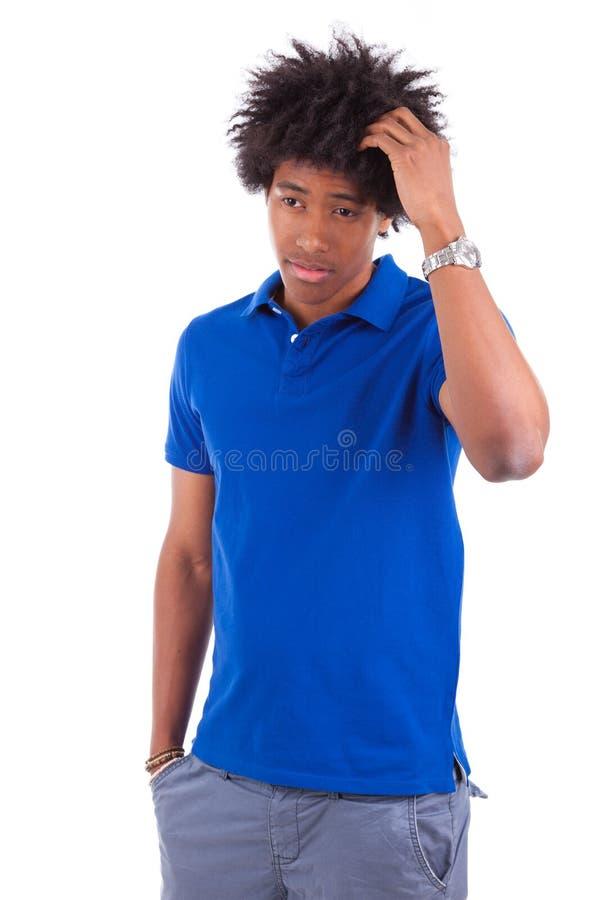 Jeune lecture adolescente noire réfléchie d'hommes livres - peo africain images stock