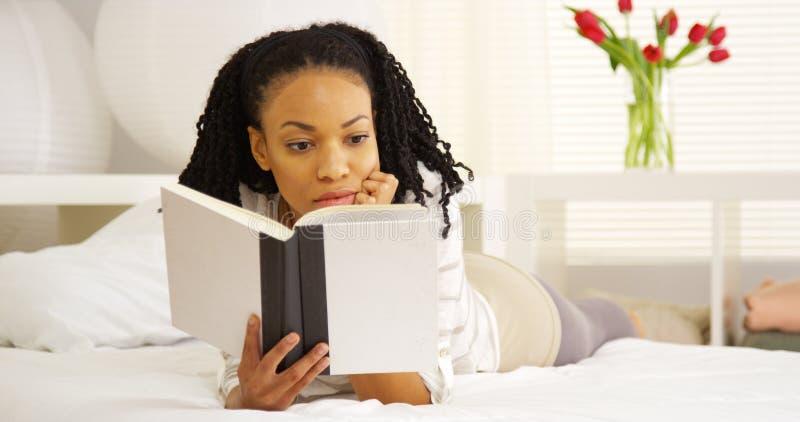 Jeune lecture de femme de couleur sur le lit photo stock