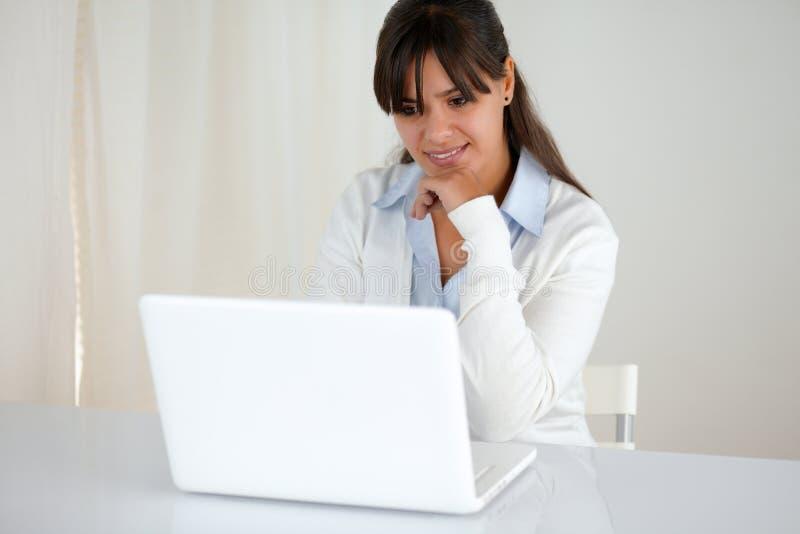 Jeune lecture femelle songeuse sur l'écran d'ordinateur portable photographie stock