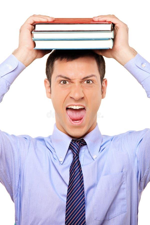 Jeune livre chargé de fixation d'étudiant au-dessus de sa tête photos stock