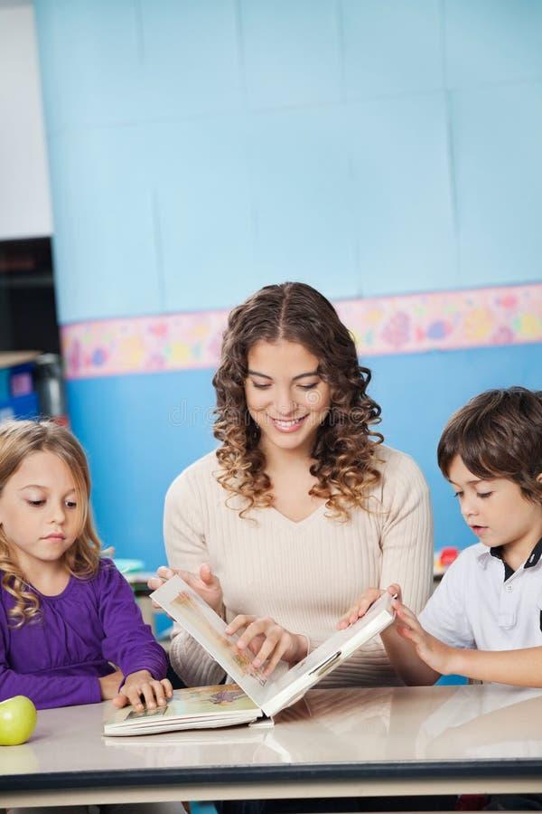 Jeune livre d'And Children Reading de professeur dedans image stock