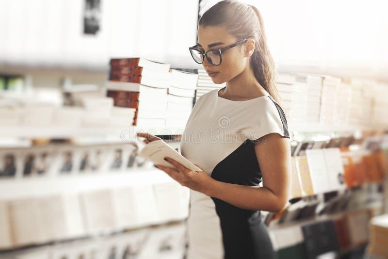 Jeune livre de lecture attrayant de femme dans une librairie à côté des étagères à livres image stock