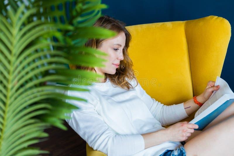 Jeune livre de lecture blond de femme ? la maison et se reposant dans le fauteuil jaune images libres de droits