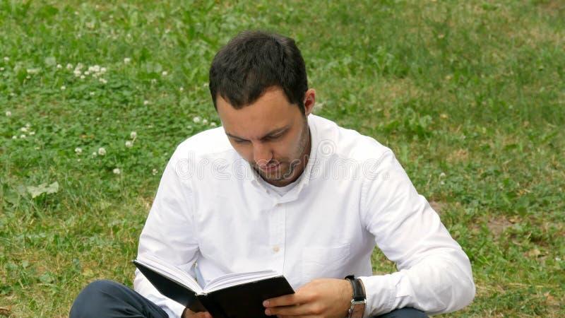 Jeune livre de lecture décontracté d'homme en nature images libres de droits