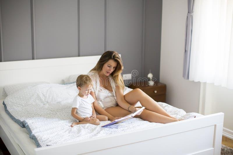 Jeune livre de lecture de mère à son petit garçon de sourire photographie stock libre de droits