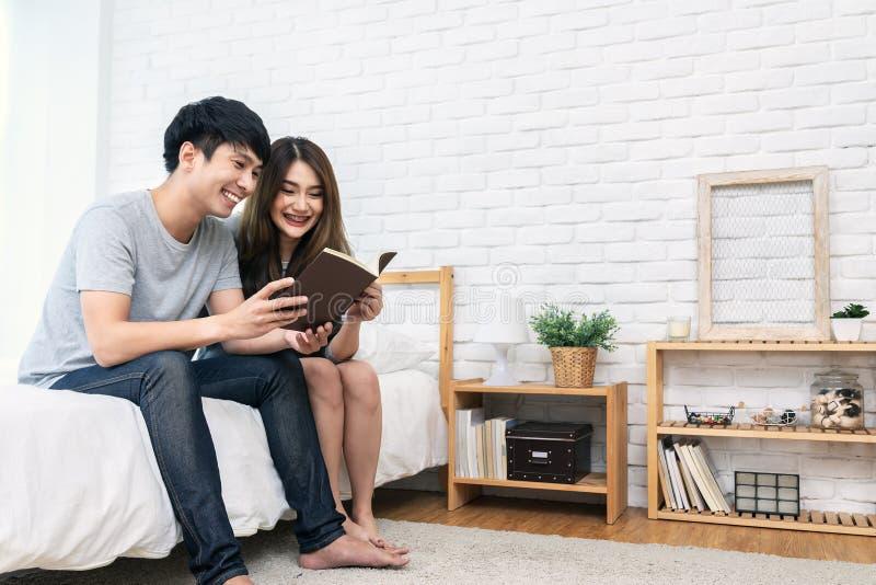 Jeune livre de lecture romantique asiatique de couples ayant le grand temps sentant ensemble la satisfaction et le positif dans l photo stock