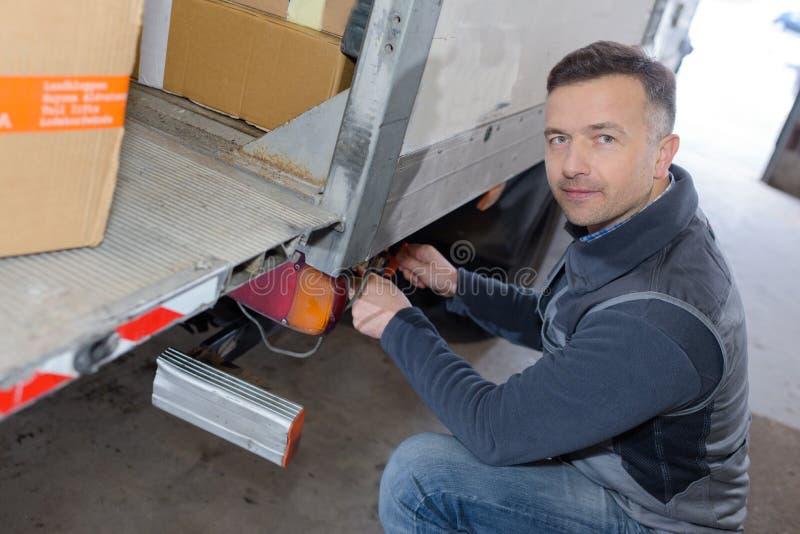 Jeune livreur avec des boîtes de chargement dans le camion image stock