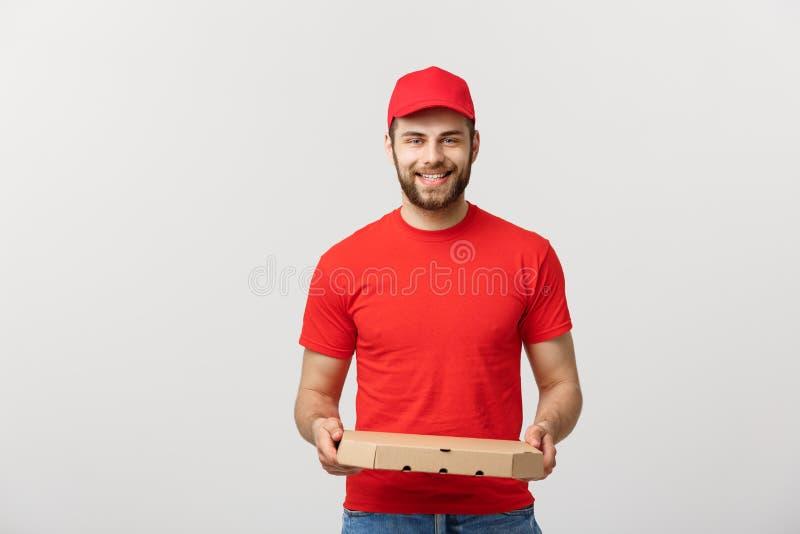 Jeune livreur gai tenant des boîtes à pizza tandis que d'isolement sur le fond blanc de studio photographie stock