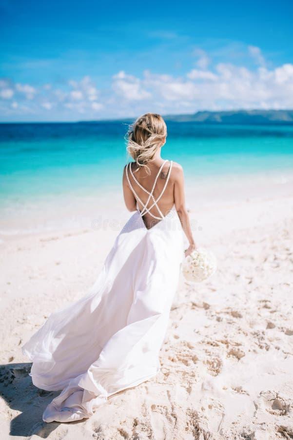 Jeune longue jeune mariée blonde de cheveux dans la robe blanche avec le dos nu se tenant sur la plage Océan tropical de turquois image libre de droits