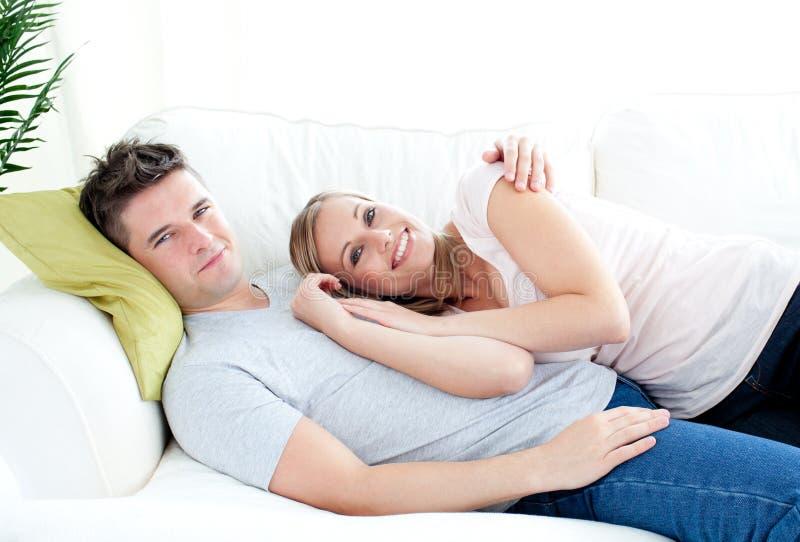 Jeune lyingo enamouré de couples ensemble sur le sofa photo libre de droits