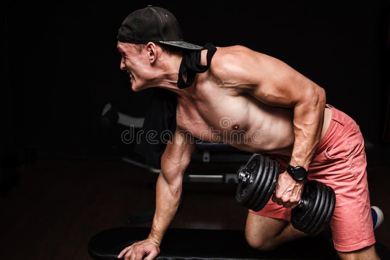 Jeune mâle adulte beau faisant des rangées d'haltère d'un-bras sur le banc dans le gymnase image libre de droits