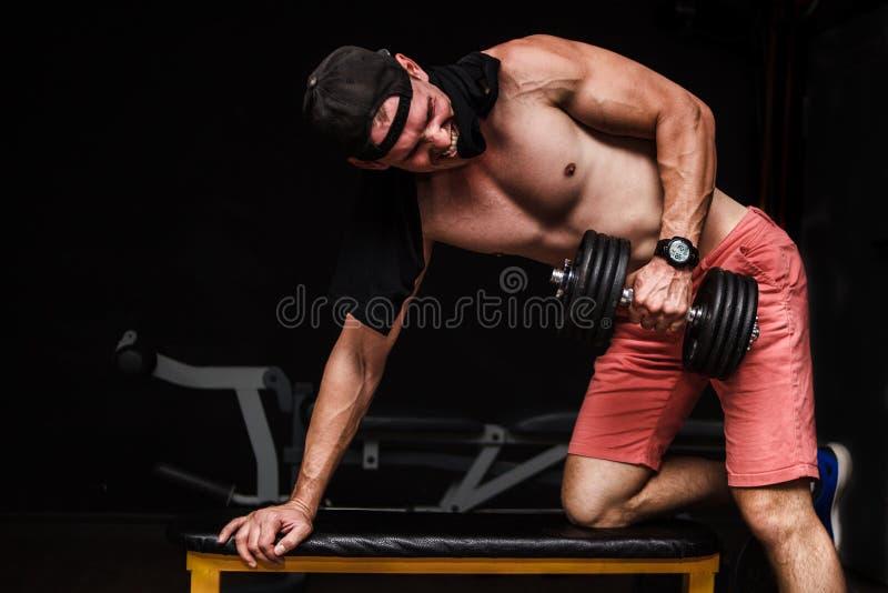 Jeune mâle adulte beau faisant des rangées d'haltère d'un-bras sur le banc dans le gymnase photo stock