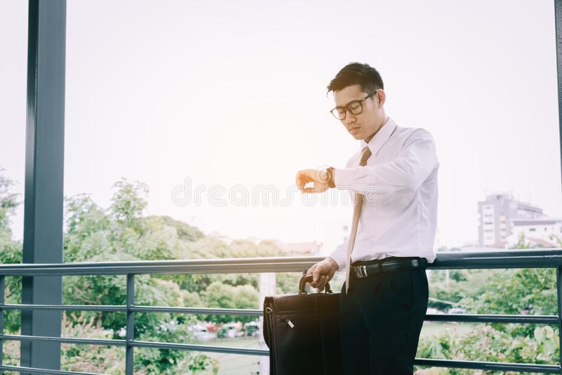 Jeune mâle asiatique se tenant vérifiant le temps et tenant des WI de serviette images stock