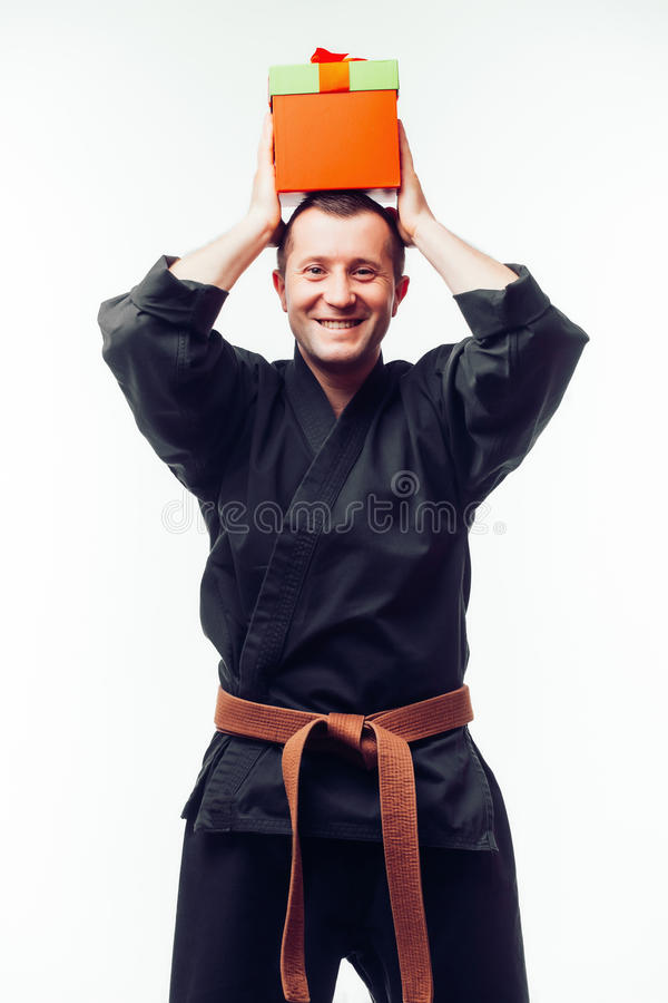 Jeune mâle avec la formation orange de combattant de karaté de ceinture avec le boîte-cadeau image stock