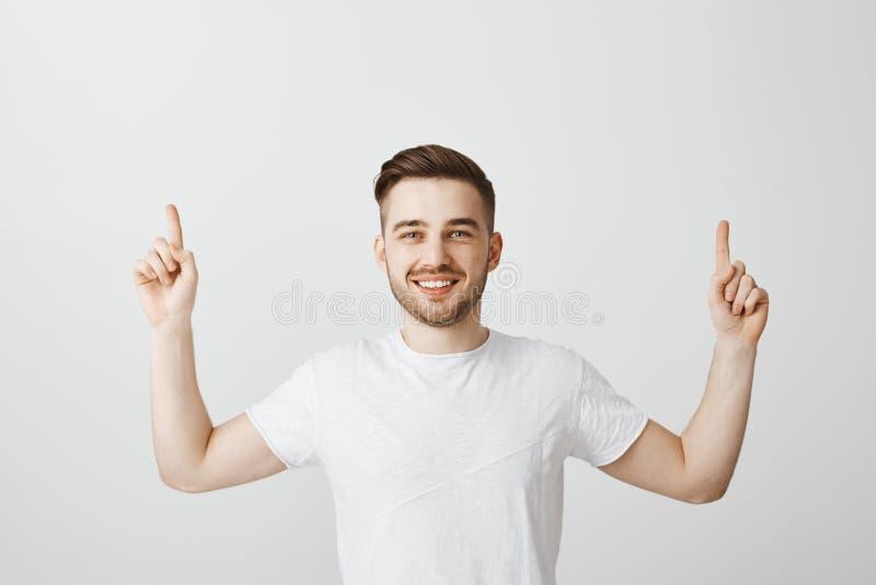 Jeune mâle caucasien amical et beau agréable avec la coiffure élégante brune soulevant des mains et se dirigeant avec photographie stock