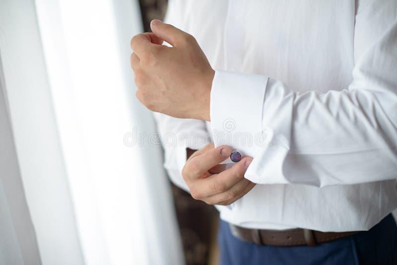 Jeune mâle caucasien obtenant habillé devant une fenêtre image stock