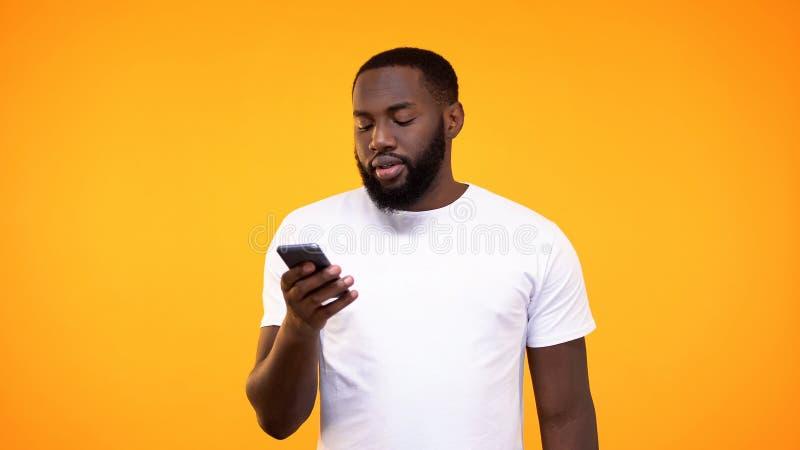 Jeune mâle dans le message blanc de lecture de T-shirt sur le smartphone, réseaux sociaux photo stock