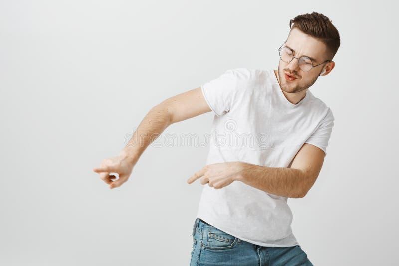 Jeune mâle européen beau satisfaisant énergique dans la danse blanche occasionnelle de T-shirt inclinant juste et entreprenant de image libre de droits