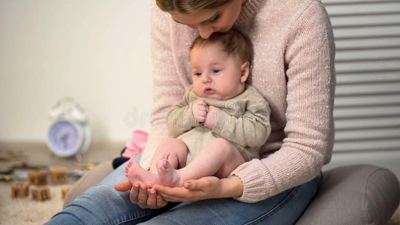 Jeune mère admirant les jambes minuscules de fils, bébé s'asseyant sur le recouvrement de la femme, bonheur photographie stock