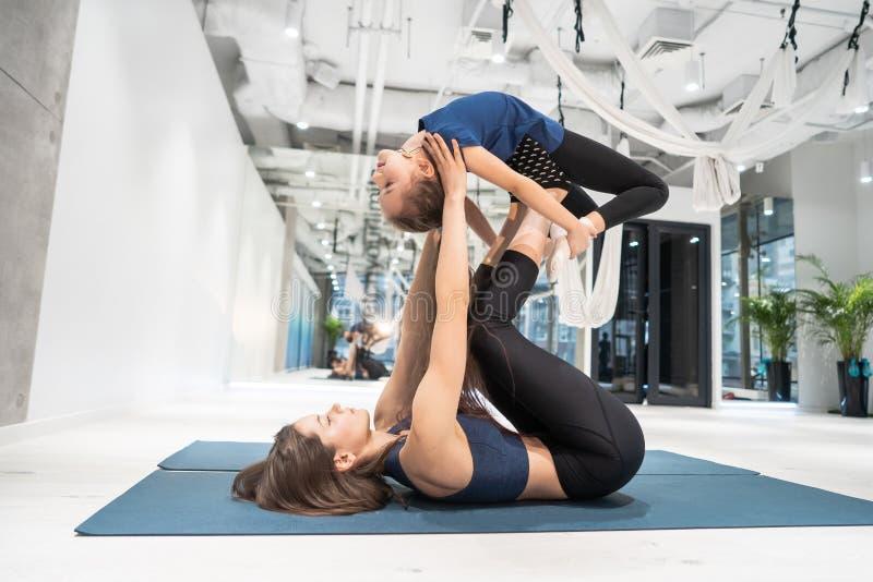 Jeune mère adulte faisant la forme physique avec sa petite fille photo libre de droits