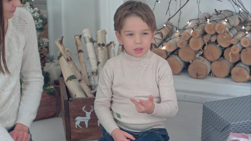 Jeune mère aidant son petit garçon comptant sur ses doigts le réveillon de Noël photos stock