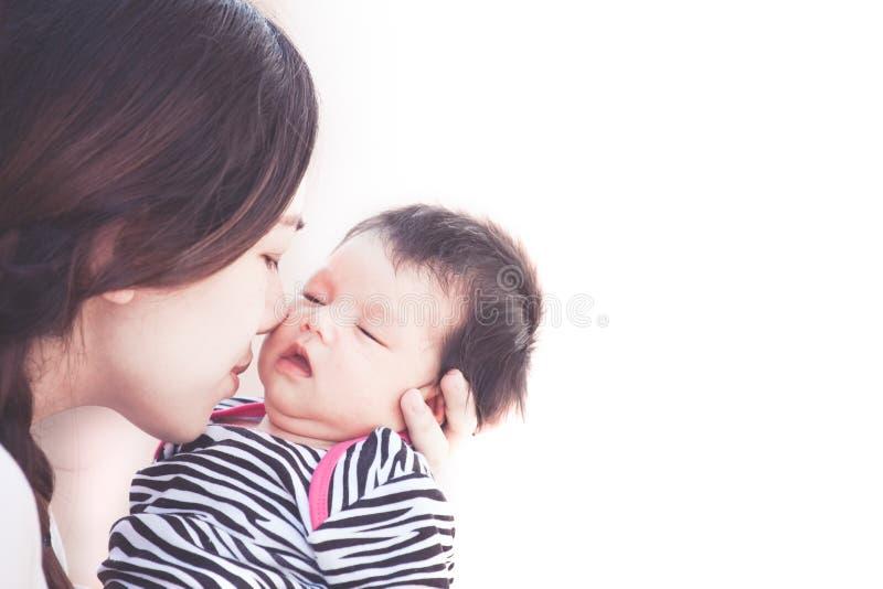 Jeune mère asiatique étreignant et embrassant son bébé nouveau-né photo libre de droits