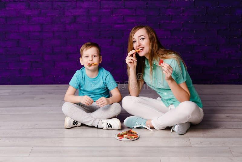Jeune mère aux cheveux longs et enfant de sept ans mangeant de la confiture d'oranges colorée images libres de droits
