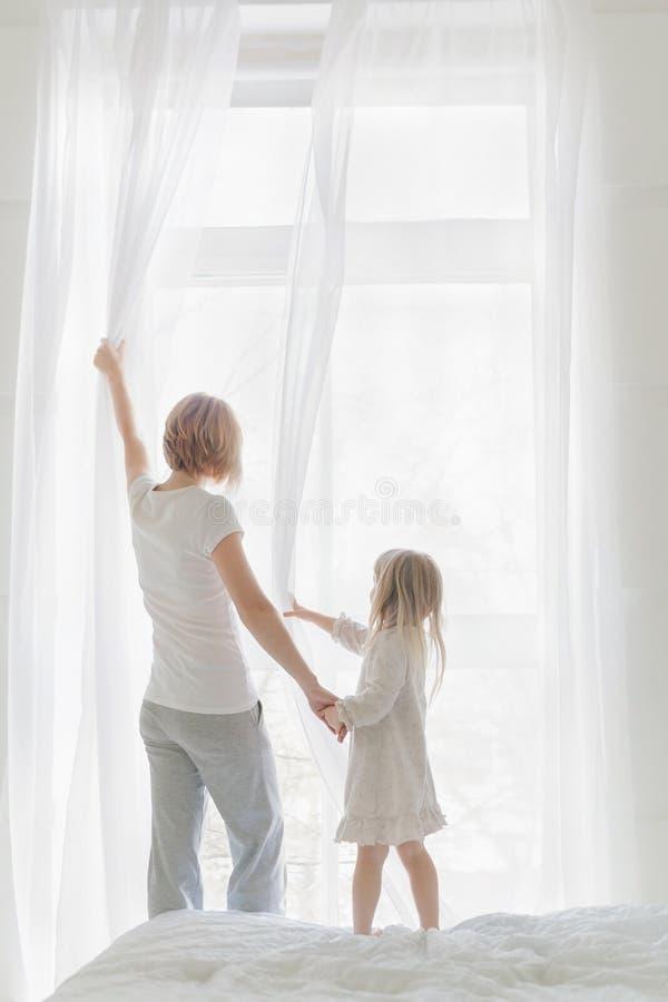 Jeune mère avec des rideaux en fenêtre d'ouverture de fille photo stock