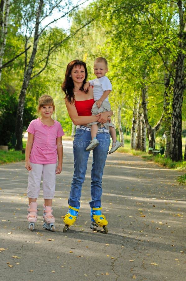 Jeune mère avec des rouleaux et ses enfants photographie stock