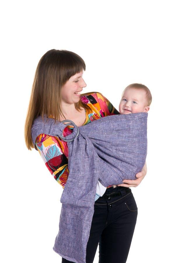 Jeune mère avec la chéri dans le sourire d'élingue   photo libre de droits