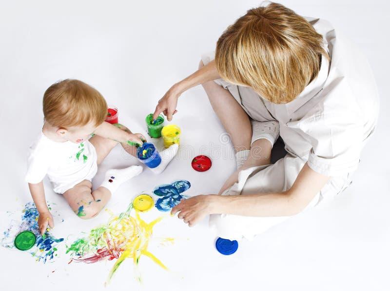 Jeune mère avec la peinture de chéri de beauté sur le fond blanc images libres de droits