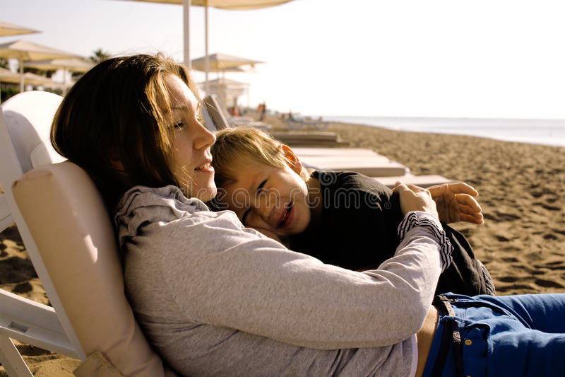 Jeune mère avec le fils se reposant sur la côte, famille heureuse parlant ensemble images stock